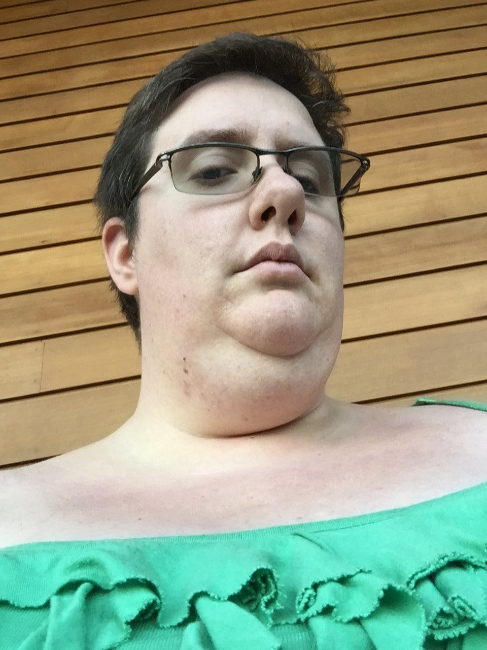 upward angle of a short -haired, fat white person with a green ruffle-y top